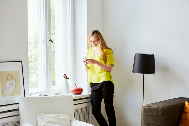 Happy young woman using mobile phone while standing by window at home