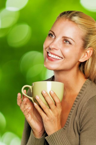 Woman holding a green mug and smiling on green bokeh background