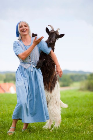 F57, farm woman caressing goat on farm, Memmingen, Bavaria, Germany