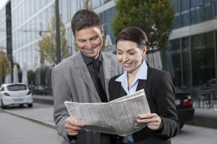 Business, Paar, Geschäftspartner lesen Börsendaten in Zeitung