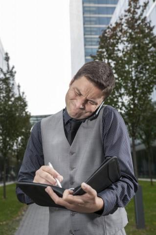 Business, Stress,  Geschäftsmann schreibt gestresst in Notizheft