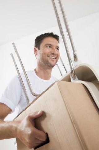 Mann bei Umzug in neuer Wohnung trägt Umzugskarton